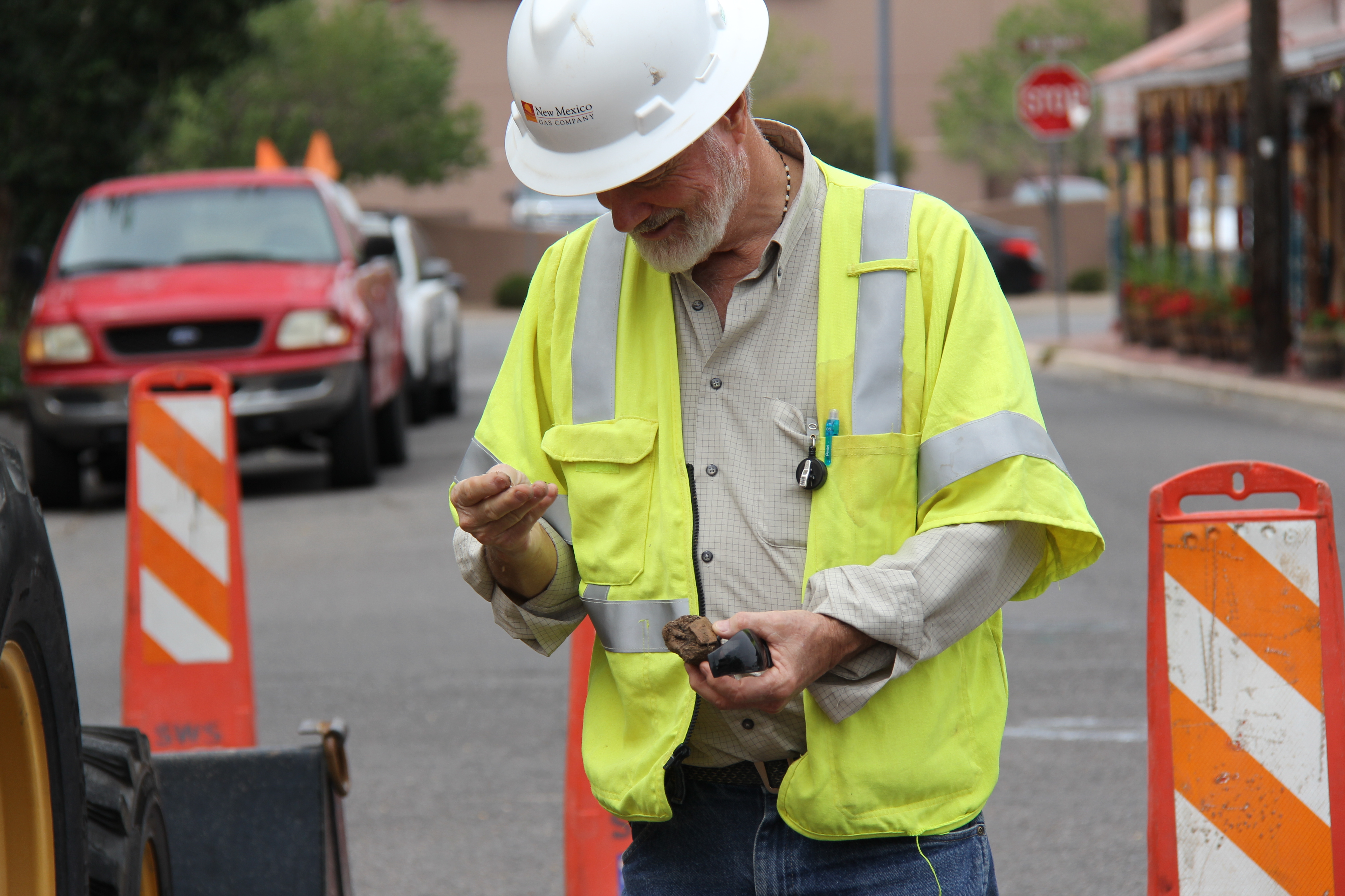 NMGC's environmentalist examines pottery found at a worksite.