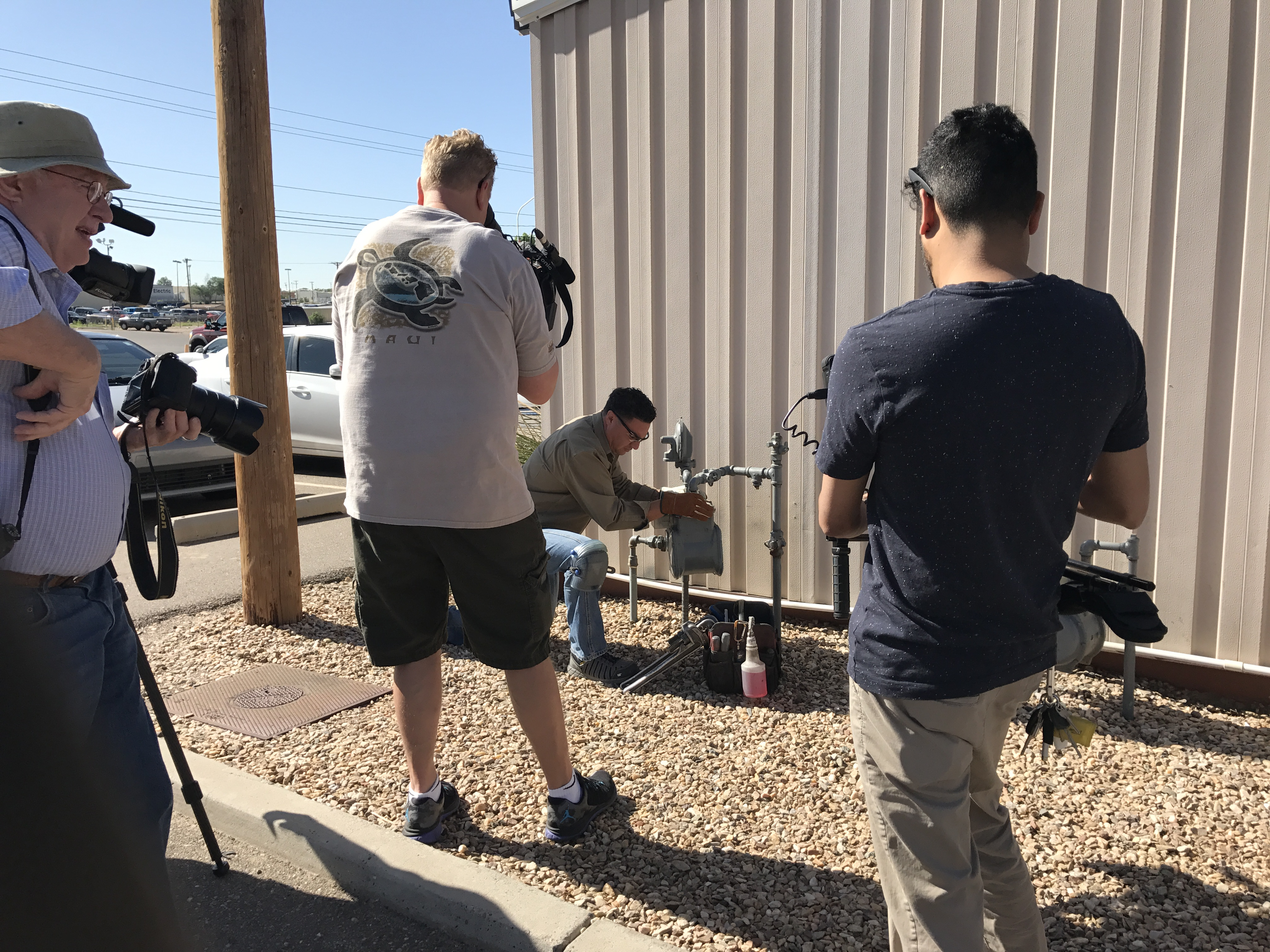 Several camera men filming an NMGC service technician while he works on a natural gas meter.